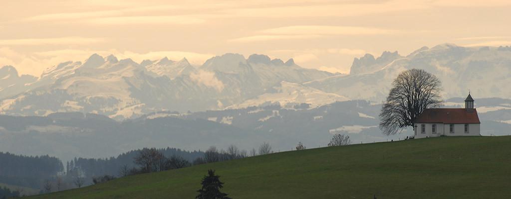 Kriche in Amtzell mit verschneitem Berg im Hintergrund